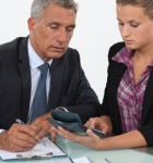 Older businessman working with younger businesswoman